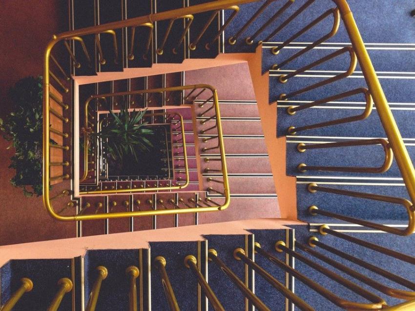 Escalera con tubo de latón en barandilla